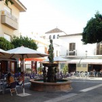 Plazas y cafeterías rodeadas de árboles y bajo un cielo azul